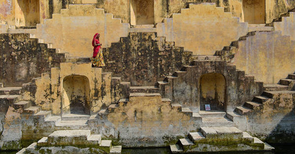 Image of local woman crossing stepwells in Jaipur, India.