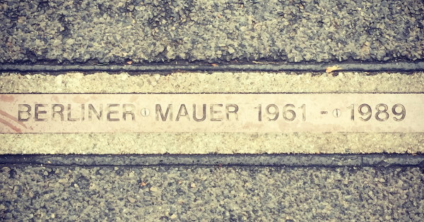 Sign in road where Berlin wall once stood